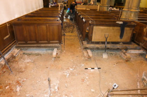 View inside church showing excavation revealing 19th C brick and timber support for pews